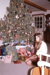 Guarded, posing in front of the Christmas tree at age 12.